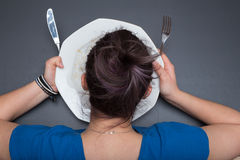 Girl is licking the plate Stock Photos