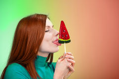Girl licking a watermelon lollipop Stock Photos