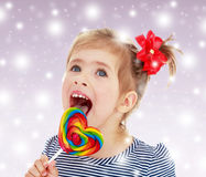 Girl licks candy on a stick Royalty Free Stock Photo