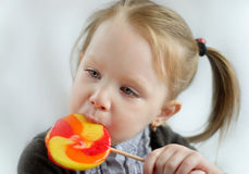 Girl licks colorful lollipop Royalty Free Stock Photo