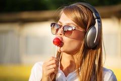Girl licks a lollipop. Music headphones Royalty Free Stock Images