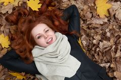 Girl lie on autumn leaves background in city park Stock Photos
