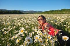 Girl lie in daisy wheel spring flower field royalty free stock photo