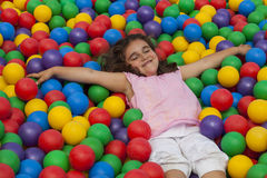 Girl lie down in a colorful plastic ball pool Royalty Free Stock Photos