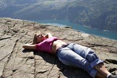 Girl lie on fjord cliff edge stock image