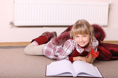 Girl lie on floor near radiator with book. Stock Photography