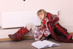 Girl lie on floor near radiator with book. Royalty Free Stock Photo