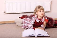 Girl lie on floor near radiator with book. Stock Photo