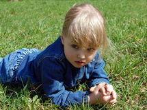 Girl lie on grass. Little girl thoughtful lie on green  grass Royalty Free Stock Images
