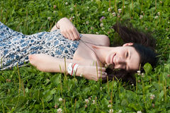Girl lie on grass field. Woman relaxing outdoors looking happy and smiling. Girl lie on grass field Royalty Free Stock Photo