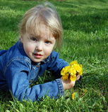 Girl lie on grass with flowers Royalty Free Stock Photography