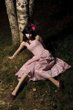 Girl lie near tree. Girl lie on the grass near the tree, may be use for broken doll concept Royalty Free Stock Images