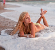 Girl lie on wet sand. Attractive young long-haired blond woman in bikini at the sea Royalty Free Stock Photo