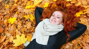 Girl lie on yellow fallen leaves in autumn forest background Royalty Free Stock Image