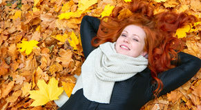Girl lie on yellow fallen leaves in autumn forest background Royalty Free Stock Photo