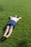 Girl lied on green grass field wiht morning light Royalty Free Stock Images