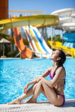 Girl lies on the backdrop of water slides. Royalty Free Stock Photography