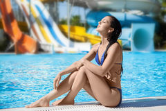Girl lies on the backdrop of water slides. Royalty Free Stock Photos