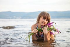 The girl lies on the beach with a bouquet of color. Beautiful view, summer day stock images