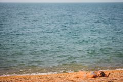 The girl lies on the beach. Great blue sea background royalty free stock images