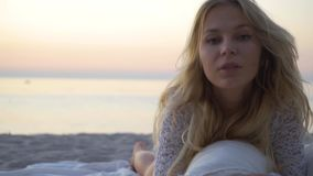 The girl lies on the beach between the pillows and blankets. sunset, romance, slow - motion, close - up. beautiful slim. The girl lies on the beach between the stock video footage