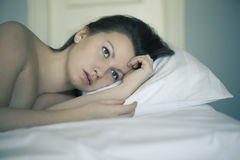 A girl lies in bed can`t fall asleep thinking and dreaming. Insomnia. Psychology. Royalty Free Stock Images