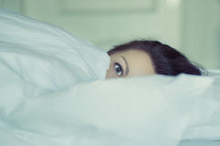 A girl lies in bed can`t fall asleep thinking and dreaming. Insomnia. Psychology. Royalty Free Stock Photo
