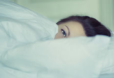 A girl lies in bed can`t fall asleep thinking and dreaming. Insomnia. Psychology. Stock Photography
