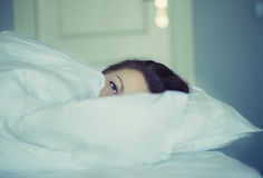 A girl lies in bed can`t fall asleep thinking and dreaming. Insomnia. Psychology. Stock Photos