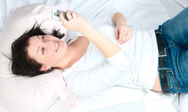 The girl lies in a bed and communicates Stock Photos