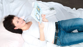 The girl lies in a bed and reads the book Royalty Free Stock Image