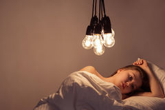 A girl lies in bed under big light bulbs can`t fall asleep. Concept picture. Insomnia. Psychology. A girl lies in bed under big light bulbs can`t fall asleep Royalty Free Stock Images