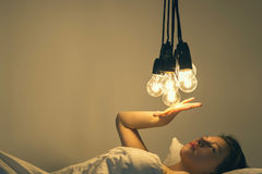 A girl lies in bed under big light bulbs can`t fall asleep. Concept picture. Insomnia. Psychology. A girl lies in bed under big light bulbs can`t fall asleep stock images