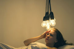 A girl lies in bed under big light bulbs can`t fall asleep. Concept picture. Insomnia. Psychology. A girl lies in bed under big light bulbs can`t fall asleep Stock Photography