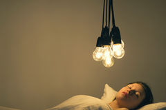 A girl lies in bed under big light bulbs can`t fall asleep. Concept picture. Insomnia. Psychology. A girl lies in bed under big light bulbs can`t fall asleep stock photos