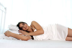 The girl lies on a bed on a white background. She is wearing a white dress. The girl sleeps Royalty Free Stock Photos