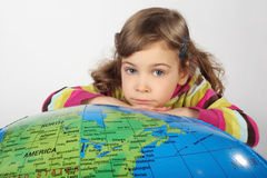 Girl lies on big inflatable globe, chin on hands Royalty Free Stock Photography