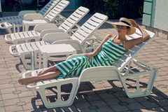 Girl lies on a chaise longue in a green striped dress. And a hat by the pool royalty free stock image