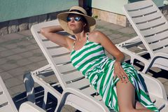 Girl lies on a chaise longue in a green striped dress. And a hat by the pool royalty free stock images