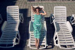 Girl lies on a chaise longue in a green striped dress. And a hat by the pool royalty free stock photography