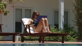 Girl Lies on Chaise Longue Typing Text on Laptop. Closeup nice girl lies on wood chaise longue near pool typing text on modern laptop against white house stock video footage