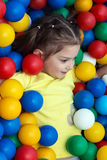Girl lies in colorful balls royalty free stock photos