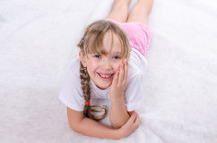 The girl lies on a floor and smiles Royalty Free Stock Photo