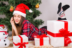 Girl lies at gifts under Christmas tree Royalty Free Stock Photography