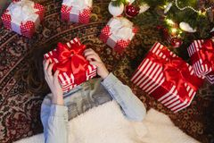 Girl lies at gifts under Christmas tree Stock Photo