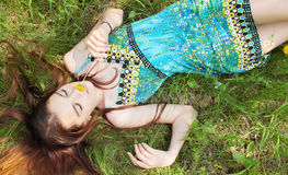 Girl lies on grass. Girl lies on the spin and smells the flower Royalty Free Stock Photography