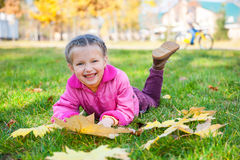 Girl lies on grass in autumn park Stock Photo