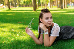 Girl lies on the grass in the park with sunglasses in his hand. Beautiful girl lying on the grass in the park in autumn Stock Images