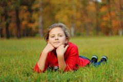 The girl lies on the green grass in the park Stock Photo