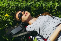 Girl lies on the green grass in sunglasses royalty free stock image